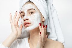 La muchacha agradable en la ropa blanca con una toalla blanca en su pelo pone una máscara cosmética en su cara foto de archivo libre de regalías