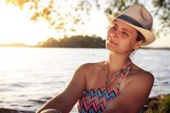 La muchacha agradable en sombrero se sienta en la orilla del lago en una tarde caliente del verano Mujer joven fuera de la ciudad Foto de archivo