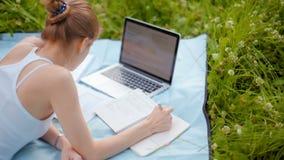 La muchacha agradable está estudiando en parque con el ordenador portátil y el cuaderno en el verano en hierba almacen de metraje de vídeo