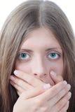La muchacha agradable que cubre las palmas de una boca Foto de archivo