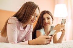 La muchacha agradable que mira su más joven envía mensajes Fotos de archivo