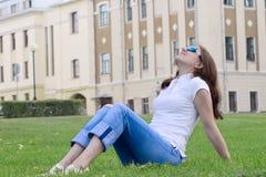 La muchacha agradable que tiene un resto en una hierba Imagenes de archivo