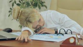 La muchacha agradable se cayó dormido en el trabajo en oficina almacen de video