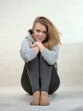 La muchacha agradable se sienta abrochando las manos de las rodillas Imagen de archivo