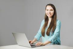 La muchacha agradable se sienta en el ordenador portátil moderno y sonríe imagen de archivo libre de regalías