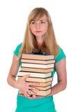 La muchacha agradable sostiene muchos libros Imágenes de archivo libres de regalías