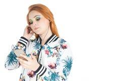 La muchacha ajusta las auriculares y la caja fuerte del teléfono celular El llevar Redheaded de la muchacha Fotos de archivo