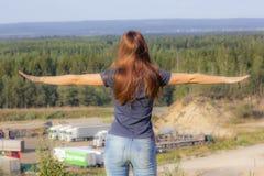 La muchacha al borde del acantilado está mirando adelante, sus brazos se separa imagenes de archivo