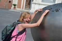 La muchacha alcanza divertido ruidosamente en una obra de arte en la ciudad de Pisa, Italia Foto de archivo libre de regalías