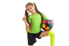La muchacha alegre con el balón de fútbol muestra los pulgares para arriba y sonríe Imagen de archivo libre de regalías