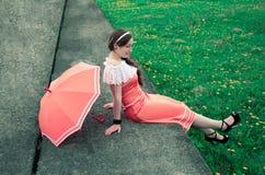 La muchacha alegre con el paraguas se sienta en un bloque de cemento en un backgroun Fotografía de archivo