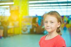 La muchacha alegre con el pelo rubio mira la cámara y las sonrisas, retrato en el fondo del centro de juego Fotos de archivo