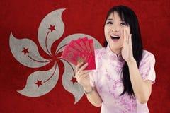 La muchacha alegre con el vestido del cheongsam sostiene el sobre Fotos de archivo libres de regalías