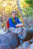 La muchacha alegre con la mochila y el hippie diseñan la ropa que se sienta en bosque Fotos de archivo libres de regalías