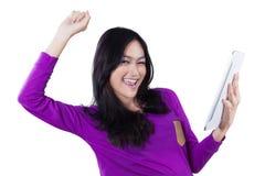 La muchacha alegre con la tableta celebra su éxito Fotografía de archivo libre de regalías