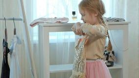 La muchacha alegre con las coletas en una falda rosada intenta en la ropa, los vestidos, los tacones altos y las danzas de la mad metrajes