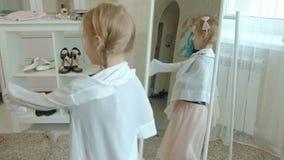 La muchacha alegre con las coletas en una falda rosada intenta en la ropa, los vestidos, los tacones altos y las danzas de la mad almacen de video