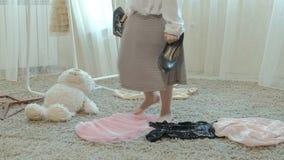 La muchacha alegre con las coletas en una falda rosada intenta en la ropa, los vestidos, los tacones altos y las danzas de la mad almacen de metraje de vídeo