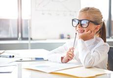 La muchacha alegre de la pequeña empresa está trabajando en oficina Fotografía de archivo