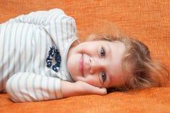 La muchacha alegre de tres años que miente en el sofá Imagenes de archivo