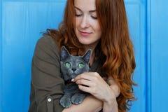 La muchacha alegre del pelirrojo juega con su gato azul Imagenes de archivo