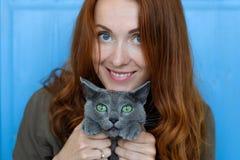 La muchacha alegre del pelirrojo juega con su gato azul Foto de archivo libre de regalías