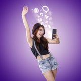 La muchacha alegre disfruta del entretenimiento en smartphone Imágenes de archivo libres de regalías