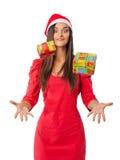 La muchacha alegre en el sombrero del ayudante de Papá Noel coge sus regalos de la Navidad Foto de archivo libre de regalías