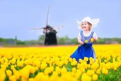 La muchacha alegre en traje holandés en tulipanes coloca con el molino de viento Imagenes de archivo