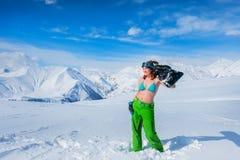 La muchacha alegre en un traje de baño lleva a cabo un tablero de la snowboard en su shoul Fotografía de archivo
