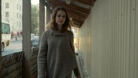 La muchacha alegre entra en un de madera pasa encendido una calle de la ciudad con la circulación densa en otoño almacen de metraje de vídeo