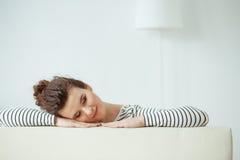 La muchacha alegre está descansando en su apartamento imagenes de archivo