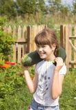 La muchacha alegre está en el huerto, recogiendo el calabacín Imagen de archivo libre de regalías