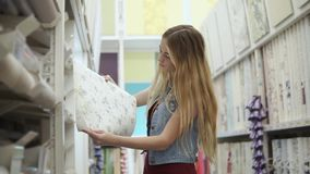 La muchacha alegre está mirando en un papel pintado en bobina en una tienda y un sueño almacen de metraje de vídeo
