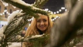 La muchacha alegre feliz cerca de la rama del abeto en ramas de árbol de navidad de la nieve con nieve está en el primero plano almacen de video
