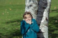 La muchacha alegre feliz con la reacción divertida cubierta en sombras y sol irradia, ocultando detrás de los árboles de abedul e Imagen de archivo