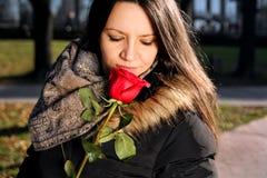 La muchacha alegre huele la rosa del rojo y goza del olor fotos de archivo
