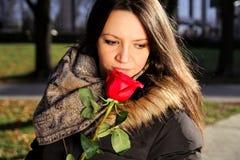 La muchacha alegre huele la rosa del rojo y goza del olor imagenes de archivo