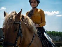La muchacha alegre joven monta en un caballo marrón Entrenamiento del montar a caballo la niña está montando un caballo Imagen de archivo