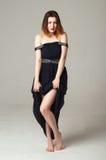 La muchacha alegre levantó su vestido negro Fotos de archivo libres de regalías