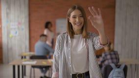 La muchacha alegre mira en la cámara y las demostraciones gesticulan la autorización Estudiante en la sala de clase V?deo 4K almacen de metraje de vídeo
