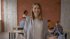 La muchacha alegre mira en la cámara y muestra el gesto de pulgares para arriba Estudiante en la sala de clase v?deo 4 k almacen de metraje de vídeo