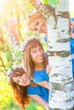 La muchacha alegre mira hacia fuera de detrás tronco del abedul Fotografía de archivo libre de regalías