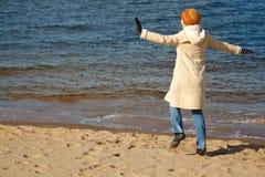 La muchacha alegre recorre en la playa en día solar del otoño Foto de archivo
