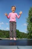 La muchacha alegre salta en el trampolín Foto de archivo