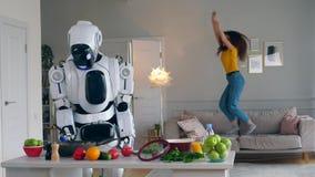 La muchacha alegre salta en un sofá mientras que un robot cocina la cena almacen de metraje de vídeo