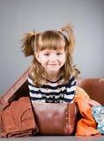 La muchacha alegre se sienta en una maleta vieja Foto de archivo