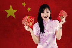 La muchacha alegre sostiene el sobre con la bandera de China Imágenes de archivo libres de regalías