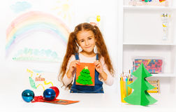La muchacha alegre sostiene la tarjeta anaranjada con el árbol de Navidad Foto de archivo