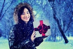 La muchacha alegre sostiene una caja de regalo Foto de archivo